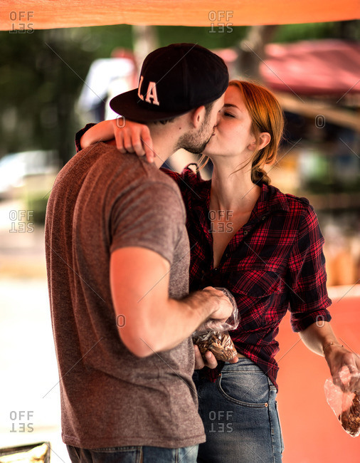 Couple kissing at an outdoor market