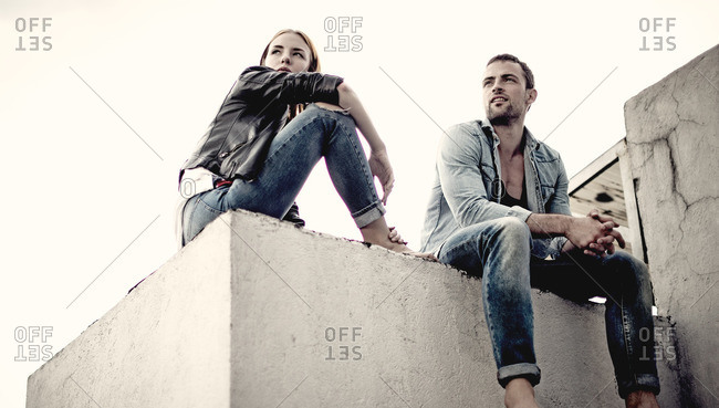 Couple sitting together on a cement structure