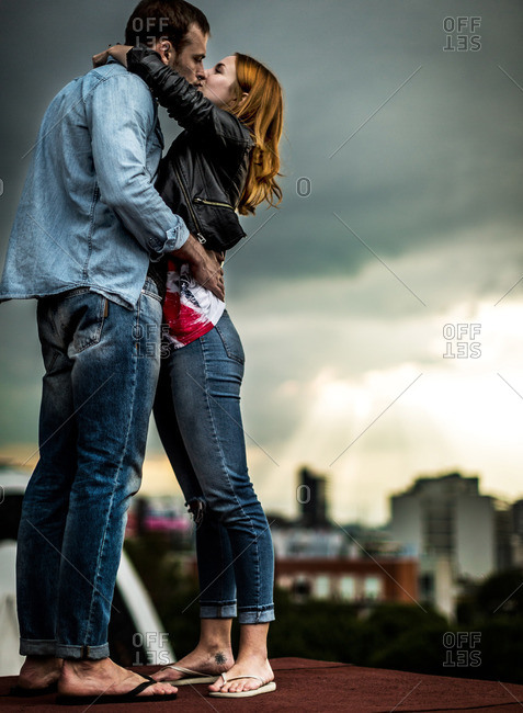 Young couple embracing and kissing on a rooftop