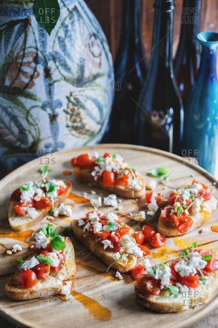 A tray of bruschetta, with a vase and bottles