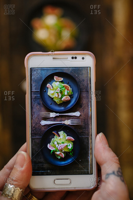 A woman takes a photo of salad with her phone