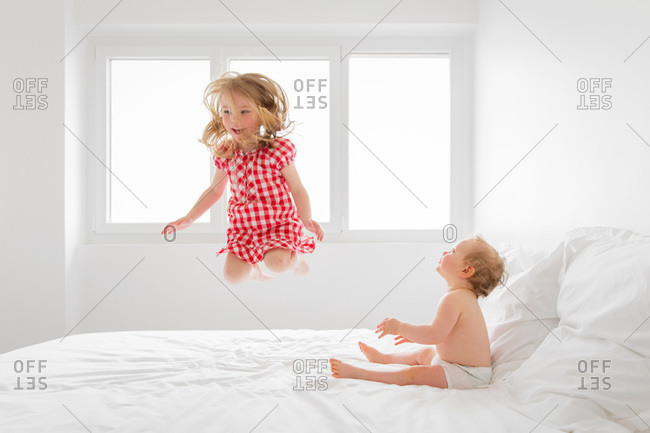 A toddler jumps on the bed while a baby watches
