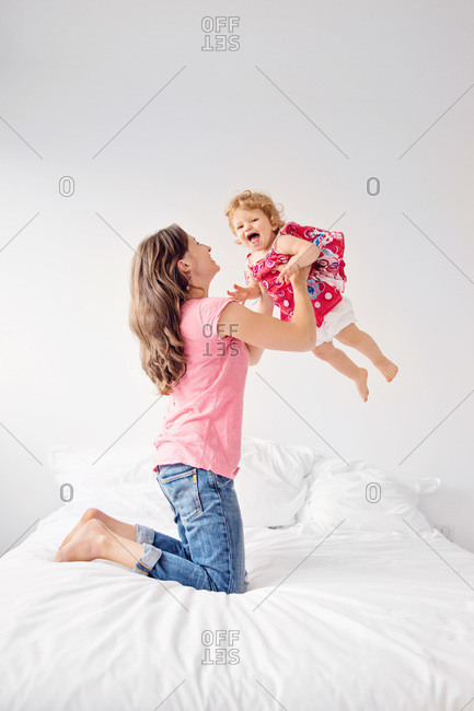 Mother lifting her daughter on a bed