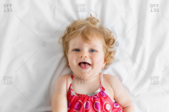 A baby girl laughing on a bed