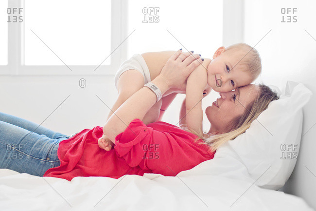 Mother holding baby up in bed