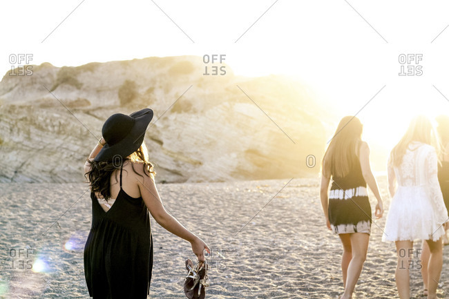 Group of young women walking on beach at sunset
