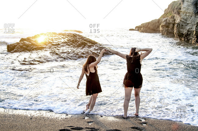 Two women holding hands walking in the ocean at sunset