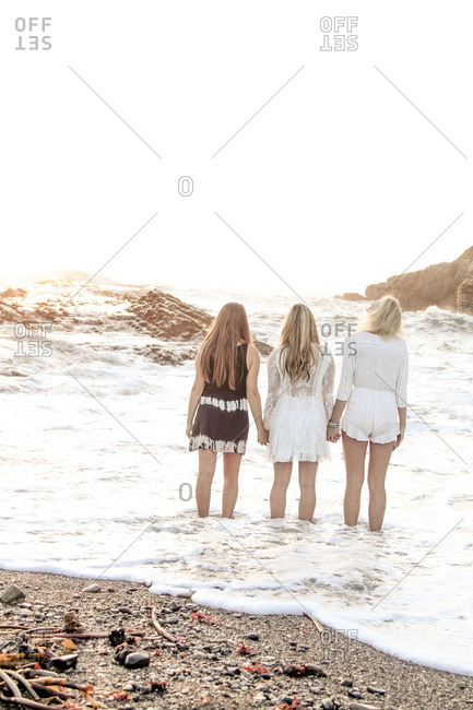 Back view of three women holding hands in the ocean at dusk