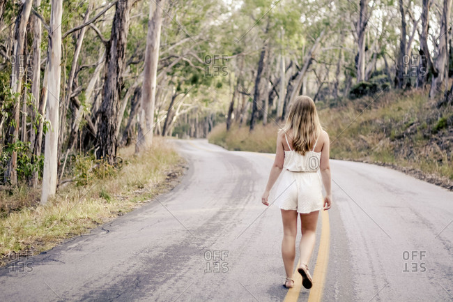 Back view of a young women walking up a wooded road