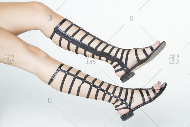 Woman's legs wearing high black strappy sandals