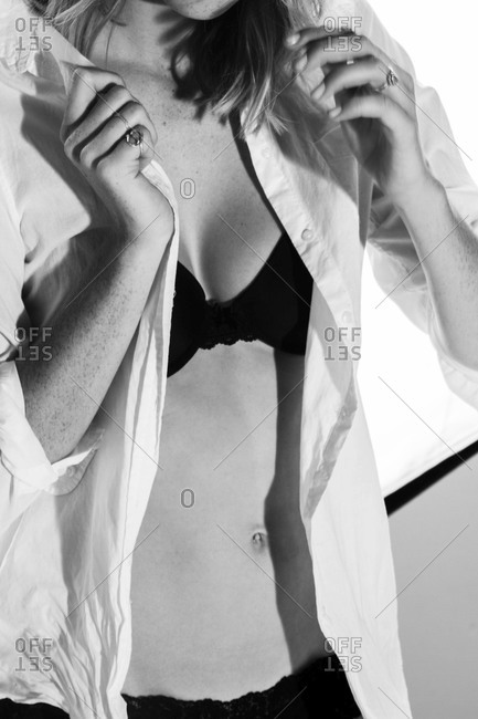 Model wearing black bra and panties with white unbuttoned shirt