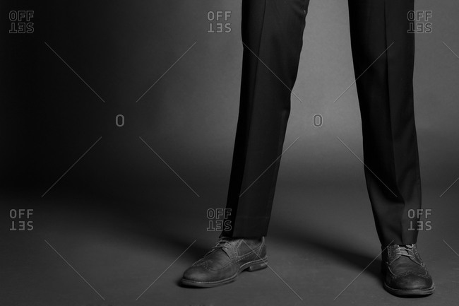 Legs of a man in tailored narrow pants and wingtip shoes