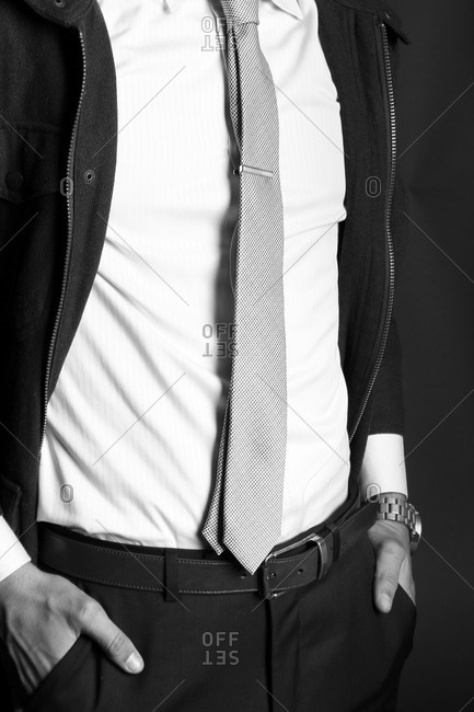 Fashion shot of man wearing a zip jacket with white shirt, tie, and black pants