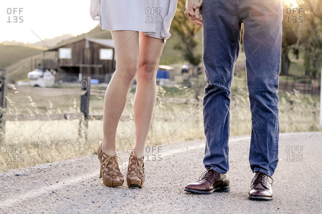 Romantic couple standing hand in hand on country road