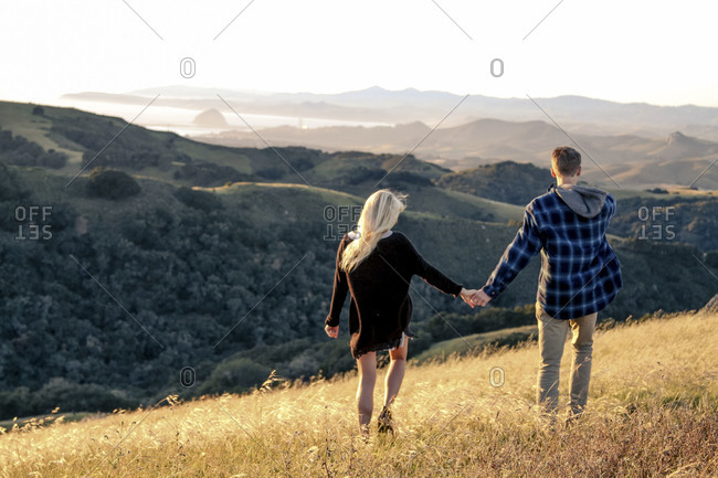 Back view of couple walking on grassy hillside overlooking mountains