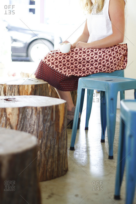 Woman in a patterned skirt sits on a blue stool in coffee shop