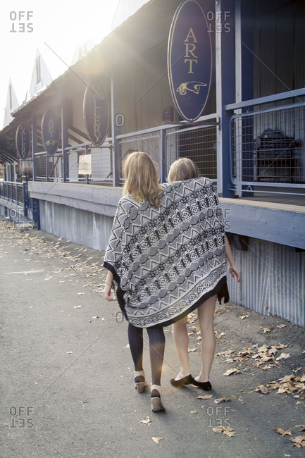 Two women wrapped in a blanket walk together near an art gallery building