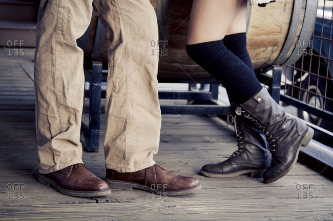 Lower legs and feet of a couple standing on a rustic wooden porch