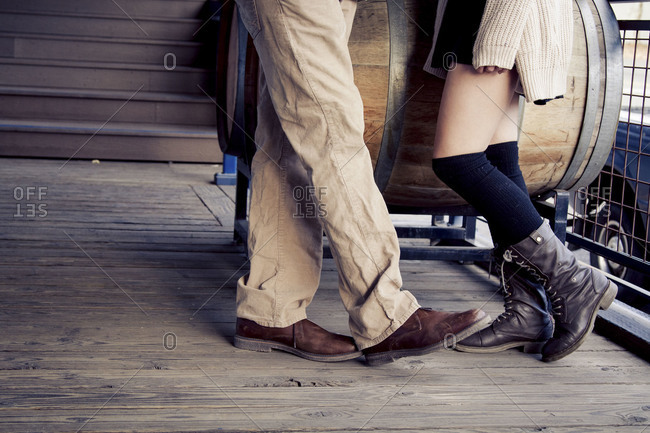 Lower legs and feet of a romantic young couple on a rustic wooden porch