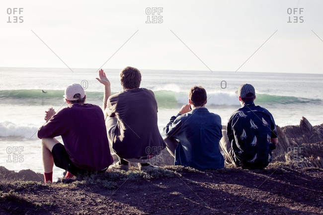Back view of four men sitting on beach