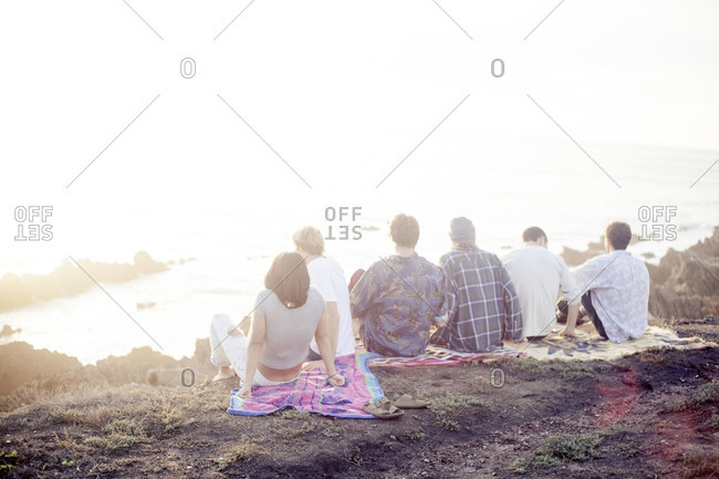 Group of friends sitting on a blanket on cliff overlooking the ocean