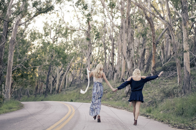 Two young women in dresses walking hand in hand up a wooded road