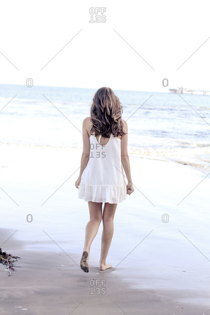 Young woman in white dress walking barefoot to the ocean