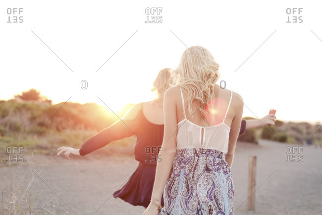 Two women walk together on beach at sunset
