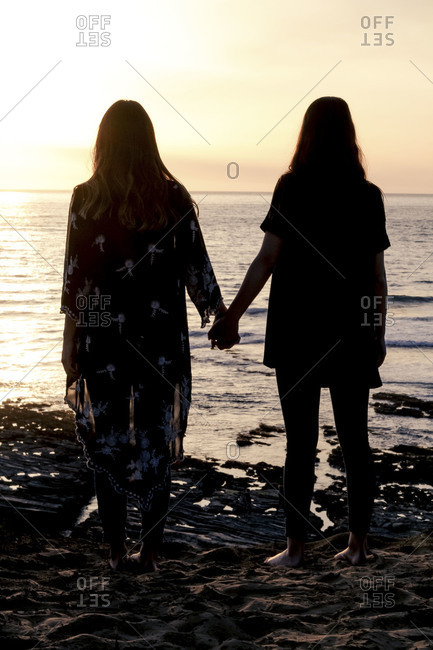 Silhouette of two young women holding hands on the beach at dusk