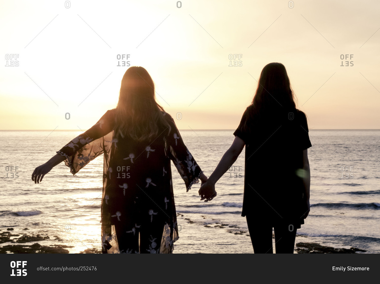 silhouette of two young women watching the sunset while