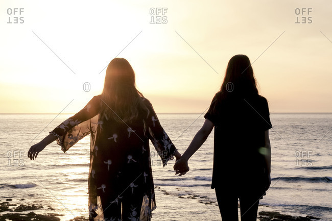 Silhouette of two young women watching the sunset while holding hands