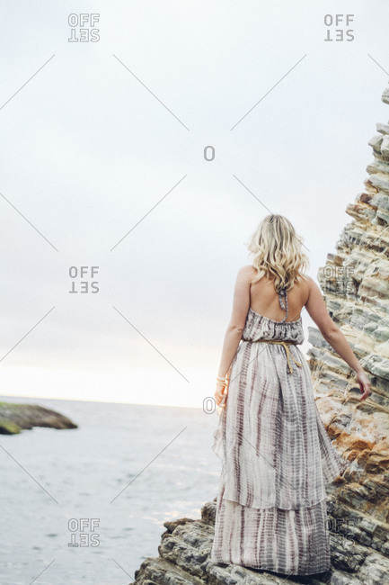 Back view of a woman in a long dress standing on rock before the ocean