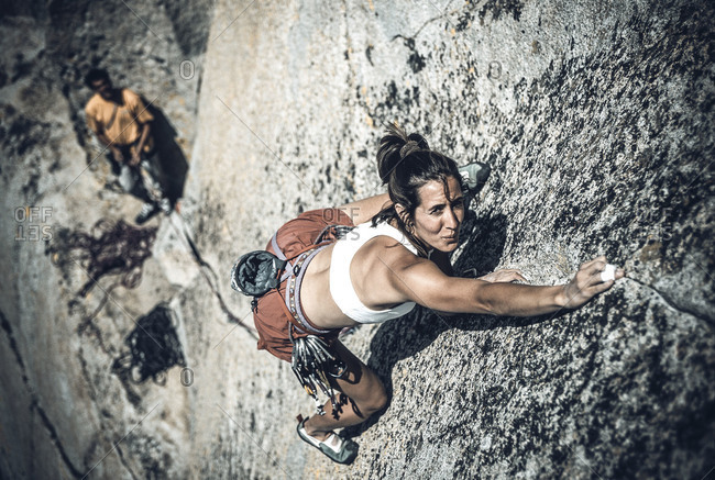 A climber struggling up a crack in a rock