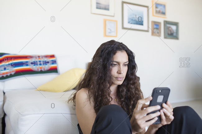 Woman using her smartphone at home on sofa