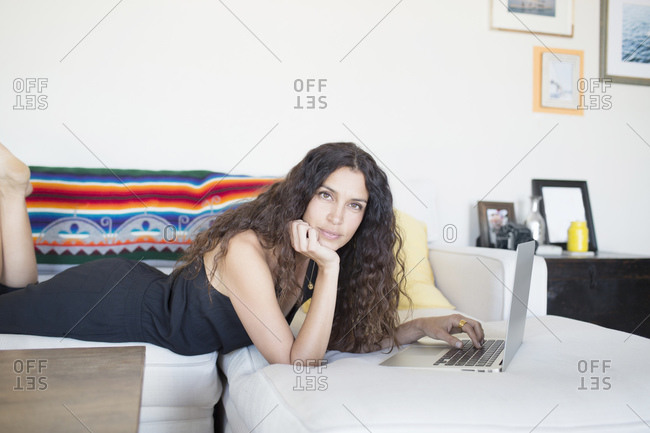 Side view of woman lying on couch using a laptop