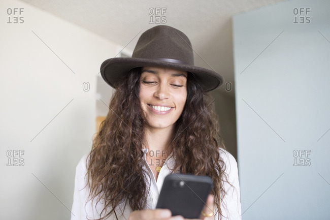 Woman in a felt hat using her smartphone