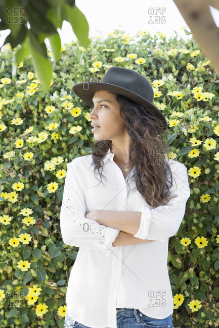 Woman in hat stands with arms crossed against a yellow flowered hedge