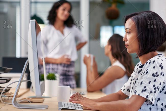 Business woman sending an email in an open-plan office