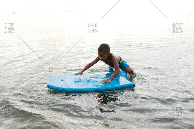 A young boy gets on a boogie board