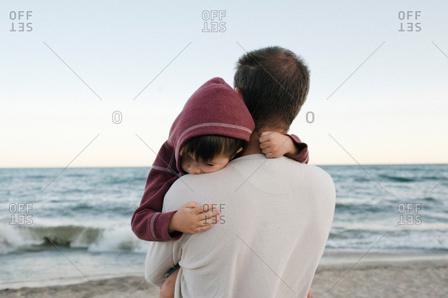 A father holds his son and looks out at the ocean