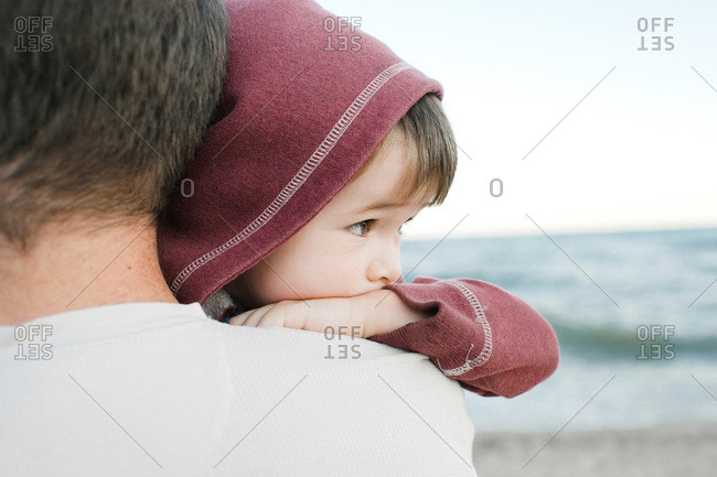 A father holds his son by the ocean