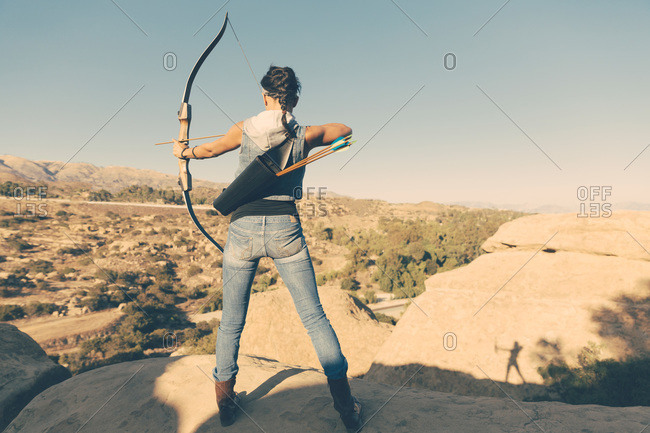 Woman with a crossbow in wilderness