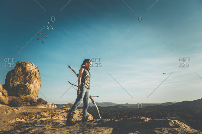 Woman with a crossbow in rocky landscape