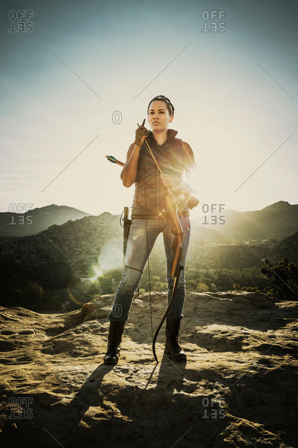 Woman with a crossbow at sunset