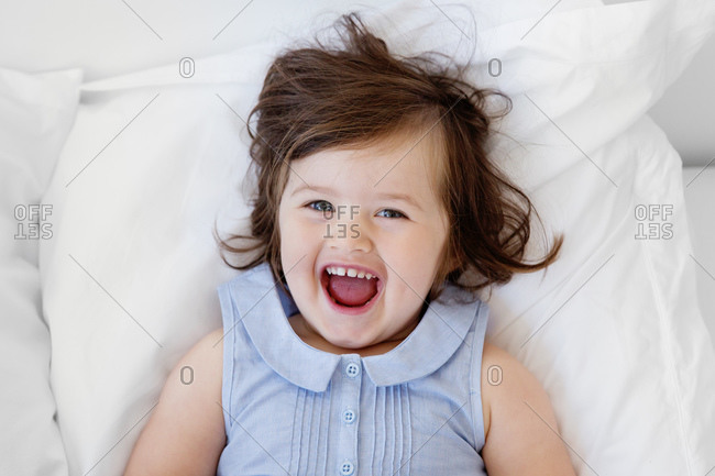 Happy little girl lying on a bed