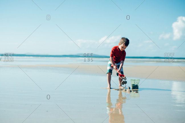 Little boy on the beach with a shovel and pail