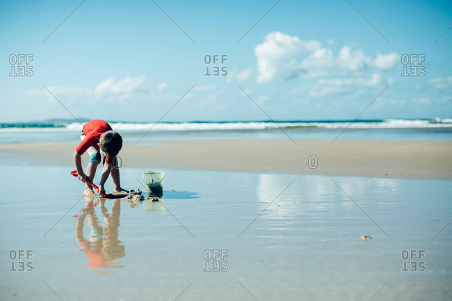 Little boy on the beach with a pail and shovel