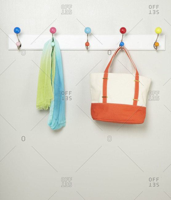 Tote bag and scarf hanging from a rack