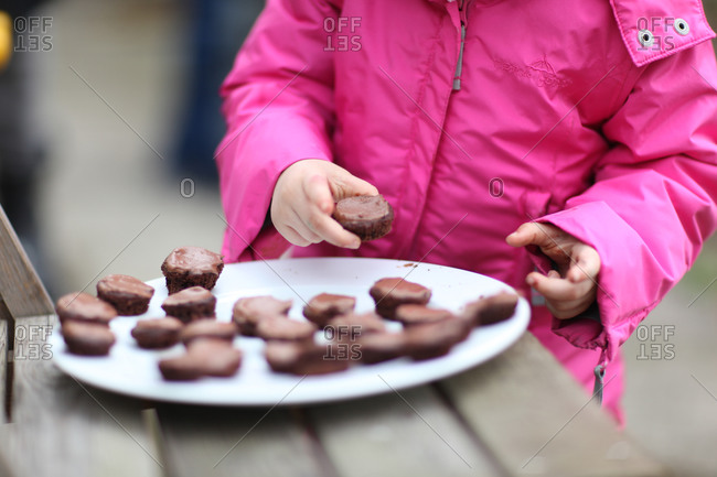 Child eating chocolate cake pieces