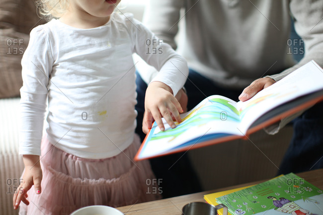 Small girl and father reading